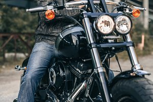 Outdoor lifestyle portrait of handsome biker man sitting on a motorcycle