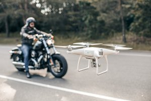Motorbike on the road riding and hovering drone