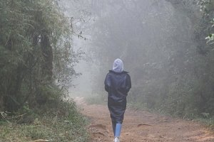 Young girl in raincoat going on wood trail during travel. Hiking woman walking in tropical wet forest. Female tourist stepping on the jungle path at mountain. Rear back view