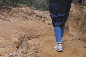 Following to female tourist in raincoat walking on stone mountain trail. Feet of woman hiking through a narrow canyon. Legs of girl in sneakers going on the rocky road. Low angle of view Close up