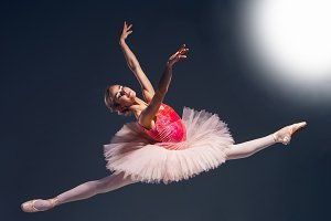 Beautiful female ballet dancer on a dark background. Ballerina is wearing pink tutu and pointe shoes.