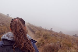 Hiking woman in raincoat with backpack walking in mountain during wet foggy weather. Young girl going on hill trail during travel. Follow to female tourist stepping on the path. Rear back view Closeup