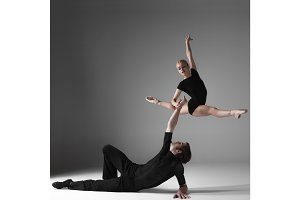 two young modern ballet dancers on gray studio background