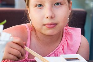 Portrait of girl eating sushi
