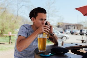 male hipster drinks beer and peanuts