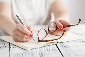 Woman writing with glasses in hand