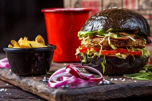 Black burger with french fries