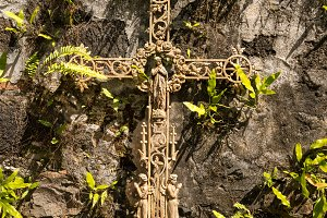 Old rusty crucifix affixed to old stone wall