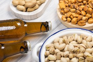 Beers with peanuts  and toasted corn on wooden background.