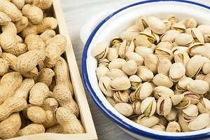 Peanuts, pistachios on a wooden tray next to toasted corn.