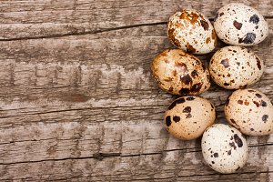 Several quail eggs on old wooden background with copy space for your text. Top view