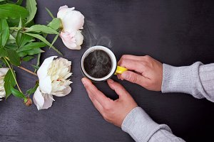 Yellow mug in female hands