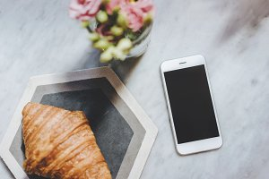 Phone with croissant and flowers