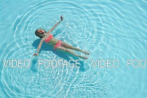 Adorable happy little girl enjoy swimming in the pool. Family summer vacation, kid relax at pool.