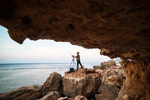Young male photographer standing in a mouth of rock cave with tripod and making photos