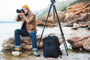 Young stylish photographer sitting on rock and making photo of sea
