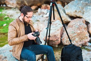 Young stylish photographer sitting on rock and watching photos he made on his camera