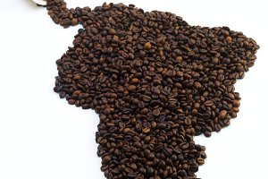 Grains of black coffee in the form of the mainland on a white background