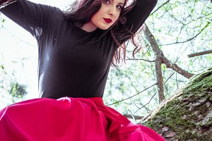 beautiful young woman on tree trunk