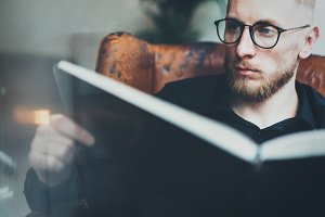 Closeup portrait of pensive bearded businessman reading book while sitting in vintage chair.Young man relaxing at home. Blurred background.Horizontal, film effect.