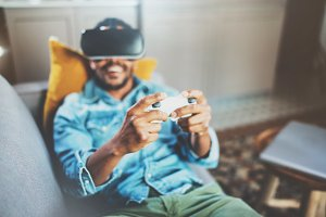 Smiling african man enjoying virtual reality glasses while relaxing on sofa.Young guy with vr headset or 3d spectacles and controller gamepad playing video game at home.Selective focus hand,blurred.