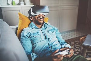 Concept of technology,gaming,entertainment and people.Bearded african man enjoying virtual reality glasses while relaxing on sofa.Happy young guy with VR headset playing video game at home.Blurred.