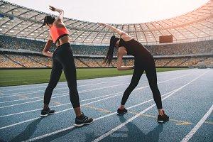 women exercising on running track