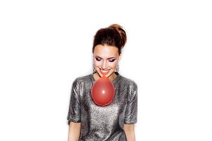 Girl blowing red balloon