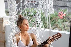 woman playing ukulele in hammock