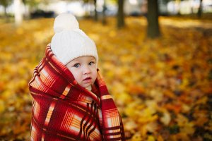 girl with blanket in autumn park