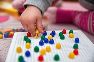 toddler plays with colorful pins