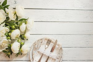 Tableware and silverware with a bouquet of white peonies on the white wooden boards
