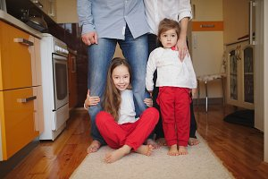 little girls hugging mom and dad for legs