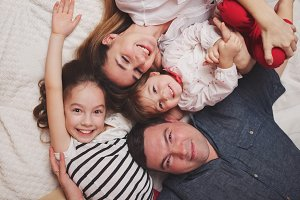 young family lying in bed at home