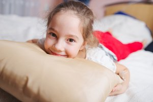young happy girl lying on pillow