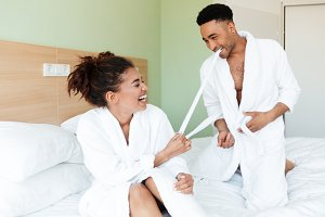 Smiling young african loving couple sitting on bed
