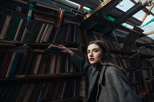 Portrait of a fashionable woman in coat taking book
