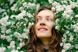 young happy smiling green-eyed woman with flowers. natural beauty