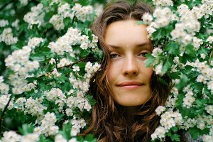 young happy smiling green-eyed woman with flowers looking at the camera. natural beauty
