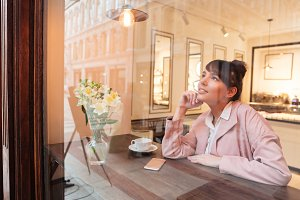 Pretty dreaming girl sitting at the cafe table