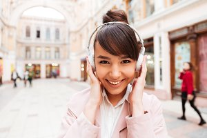 Portrait of a smiling cute girl listening music with earphones
