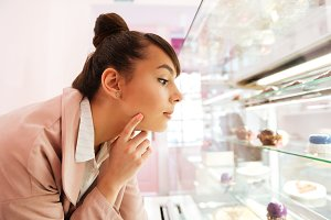 Pretty young woman choosing pastry while looking through glass showcase