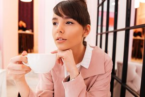 Portrait of a young attractive woman holding cup of coffee