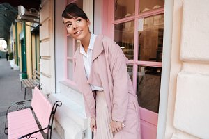 Smiling pretty girl in pink coat standing outside cafe