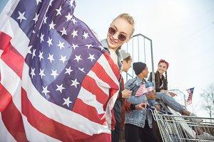 teenagers waving american flags