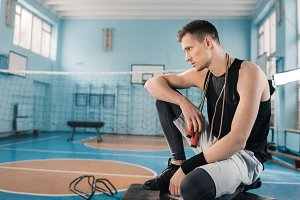 sportsman sitting with skipping rope