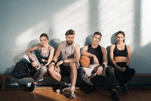 sporty people sitting on bench