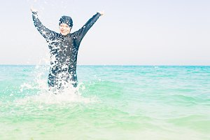 Young Woman In Burkini Splashing Water