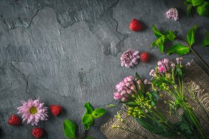 Flowers and mint on the dark stone