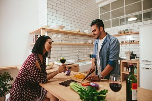 Young couple talking while cooking